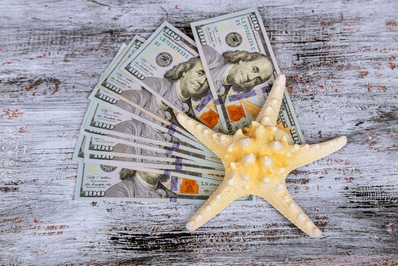 Notas de dólar do americano cem do dinheiro no áster de mar imagem de stock