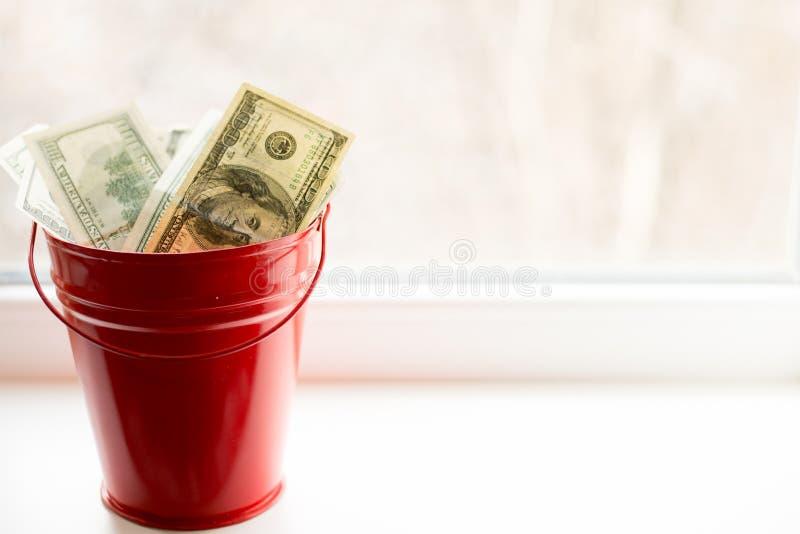 Notas de dólar no balde vermelho na janela branca Fundo claro Vista superior Muito dinheiro fotografia de stock royalty free