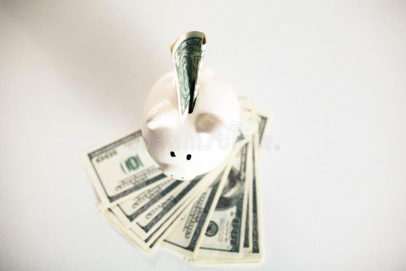 Notas de dólar que caem dentro ou que voam fora de um mealheiro cor-de-rosa imagens de stock royalty free