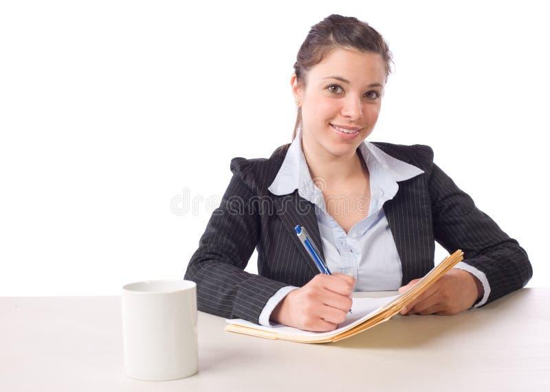 Notas de la escritura de la mujer de negocios en el escritorio imágenes de archivo libres de regalías