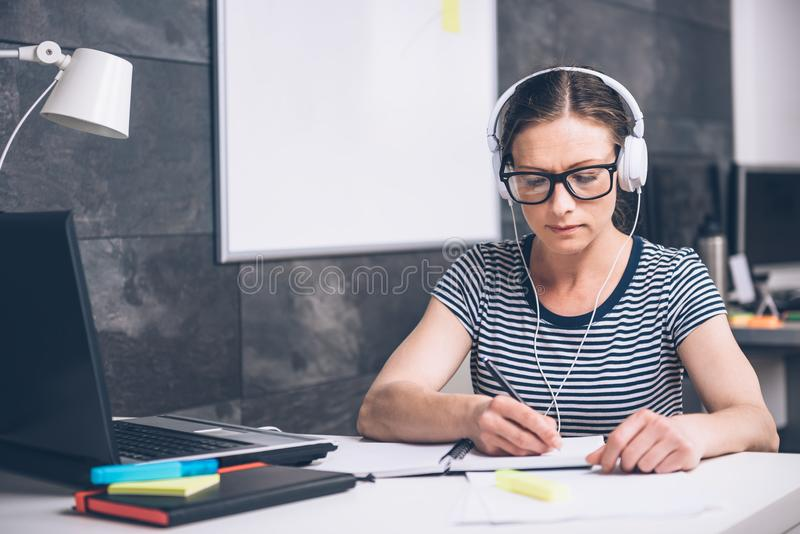 Notas de la escritura de la mujer y música que escucha en la oficina imagen de archivo