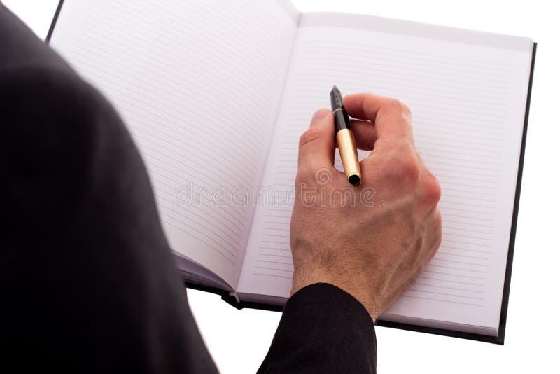 Notas de la escritura del hombre de negocios sobre una reunión imagen de archivo libre de regalías
