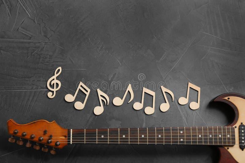 Notas de la música y cuello de la guitarra en el fondo gris, visión superior imagen de archivo libre de regalías