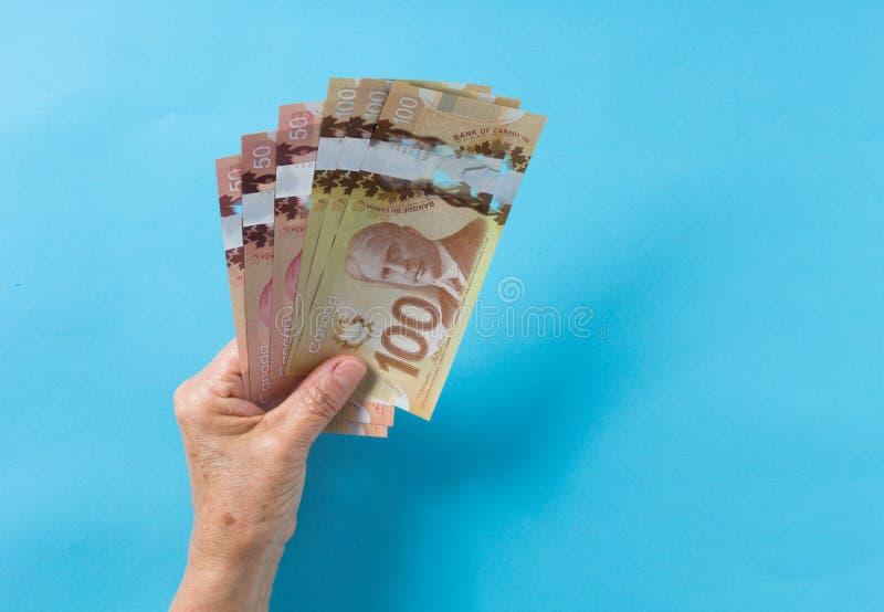 Notas de papel de Canadá Dólar Vista superior de la mano ha del ` s de la mujer mayor imagen de archivo libre de regalías