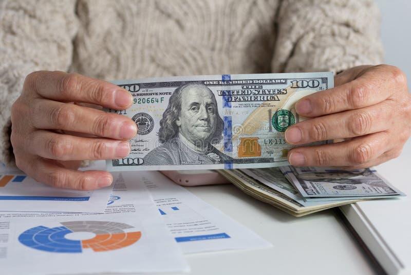 Notas de papel dos EUA Dólar Pessoa que segura papernotes na mesa imagem de stock