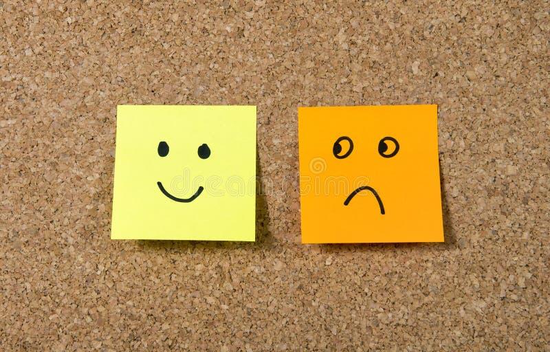 Notas de post-it sobre corkboard con la expresión sonriente y triste de la cara de la historieta en felicidad contra concepto de  imagen de archivo