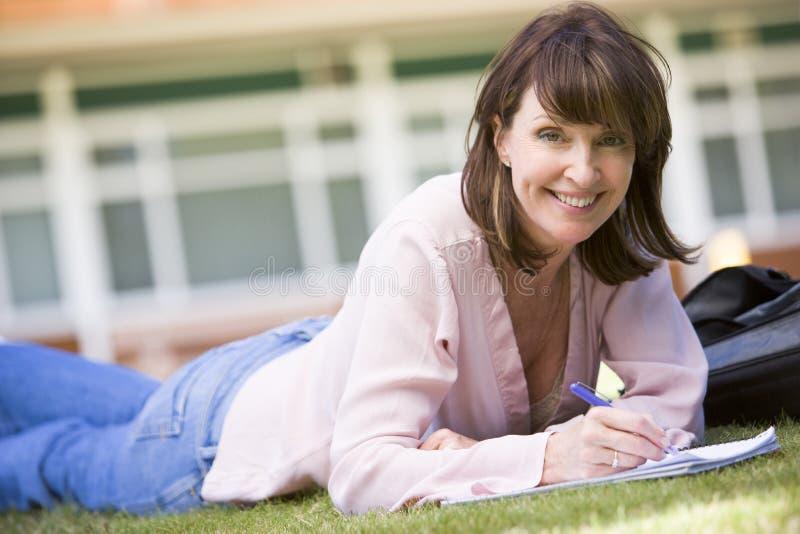 Notas de una escritura de la mujer mientras que miente en un césped del campus fotos de archivo libres de regalías