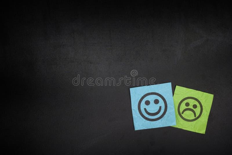 Notas do papel azul e verde com as caras felizes e tristes em blackboar foto de stock