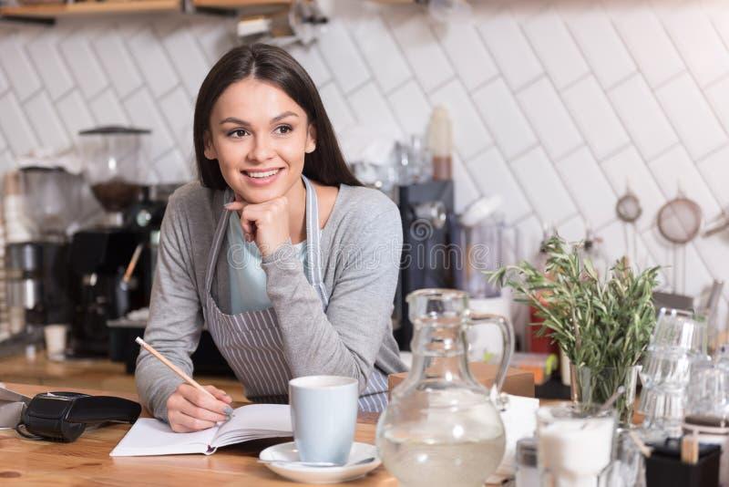 Notas encantadores atrativas da escrita da empregada de mesa durante o trabalho imagem de stock