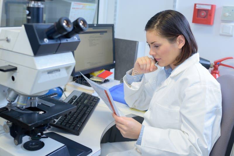 Notas fêmeas do paciente da leitura do doutor foto de stock