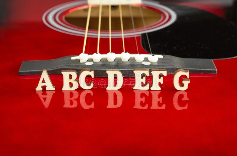 Notas musicais ABCDEFG com letras de madeira, na superfície refletindo de uma guitarra acústica Perspectiva da ponte das guitarra imagens de stock royalty free