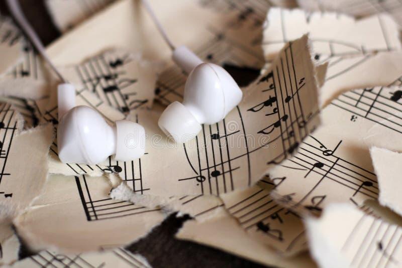 Notas musicais rasgadas, pedaços de papel, fones de ouvido brancos do vácuo foto de stock royalty free