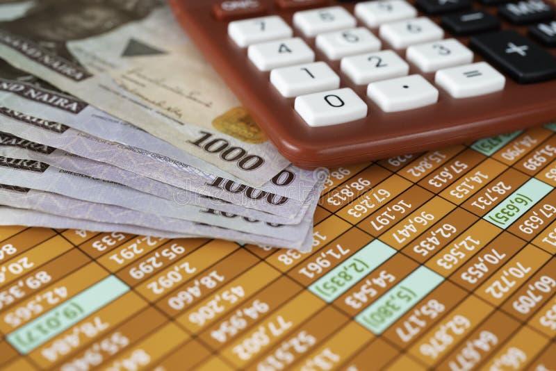 Notas nigerianas do naira com a calculadora na planilha foto de stock