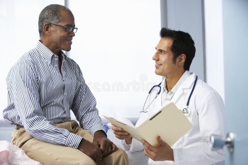 Notas pacientes masculinas da leitura do doutor In Surgery With foto de stock royalty free