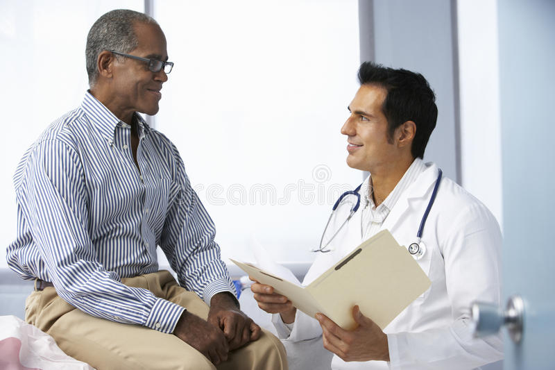 Notas pacientes masculinas de la lectura del doctor In Surgery With foto de archivo libre de regalías