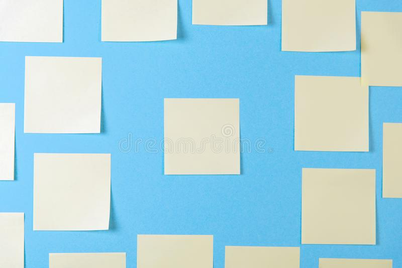 Notas pegajosas amarelas em um fundo azul, conceito da placa do trabalho do neg?cio Etiquetas amarelas do memorando na parede azu fotografia de stock