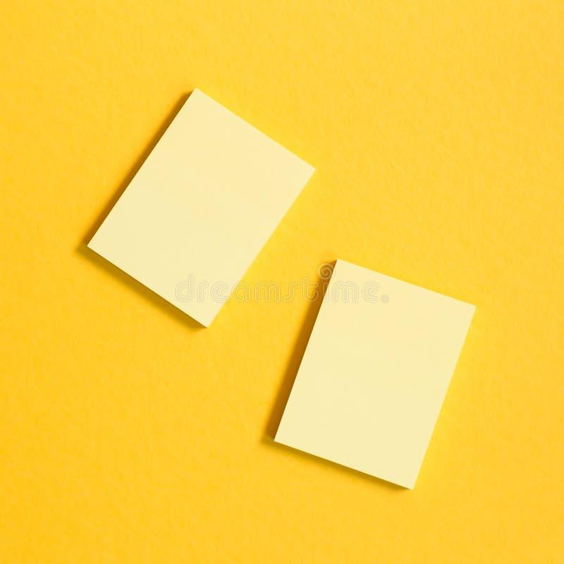 Notas pegajosas amarillas del cojín de nota sobre fondo amarillo imagen de archivo