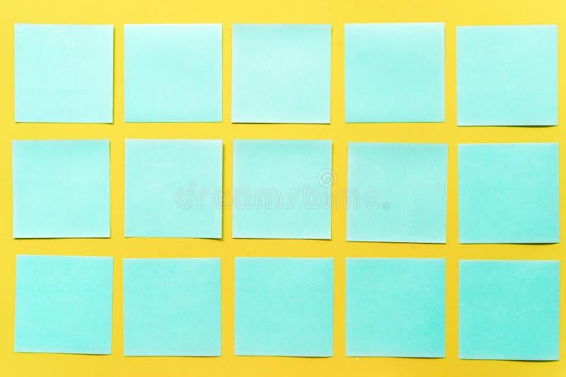 Notas pegajosas coloridas em um espa?o amarelo livre do fundo fotografia de stock