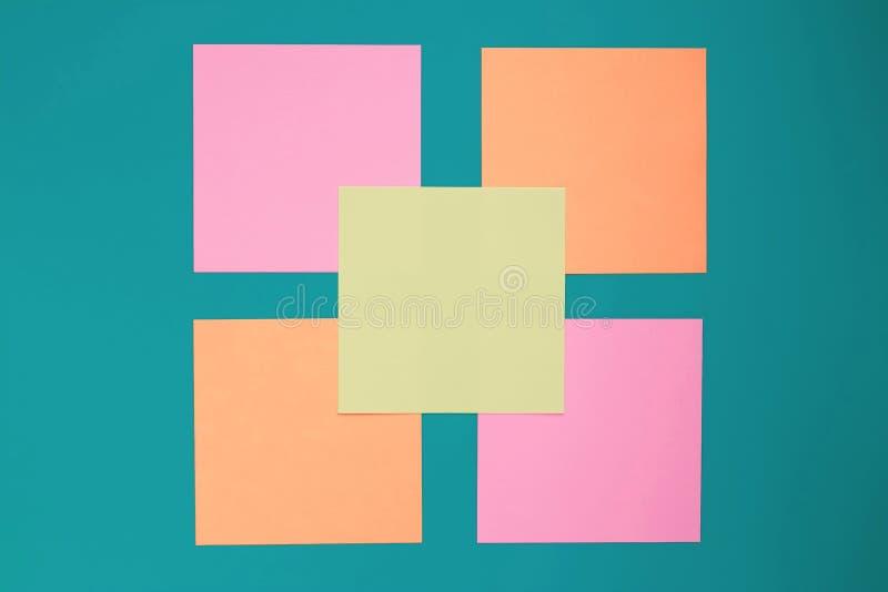 Notas pegajosas coloridas sobre tablero verde Etiquetas engomadas multicoloras en blanco en fondo azul Concepto de las hojas de o imagen de archivo libre de regalías
