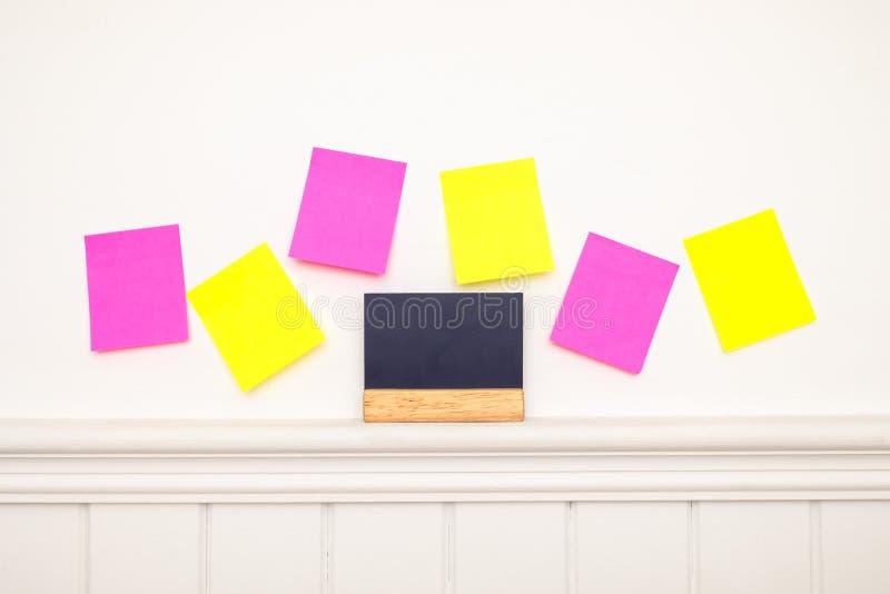 Notas pegajosas coloridas vazias e pouco quadro-negro na parede foto de stock