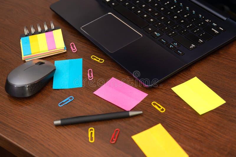 Notas pegajosas coloridas y clips de papel, pluma, ratón del ordenador y ordenador portátil derramados en el escritorio de madera foto de archivo