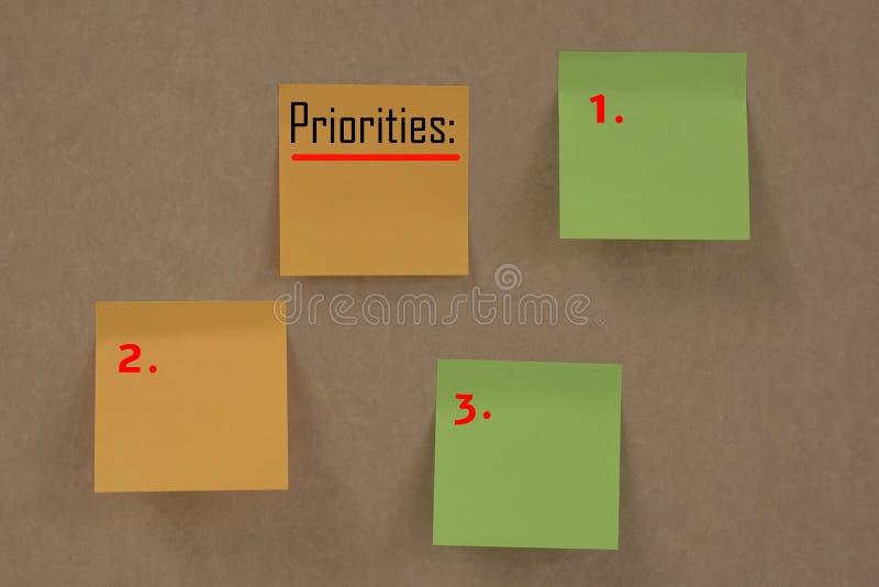 Notas pegajosas con el ` de las prioridades del ` de la palabra fotos de archivo
