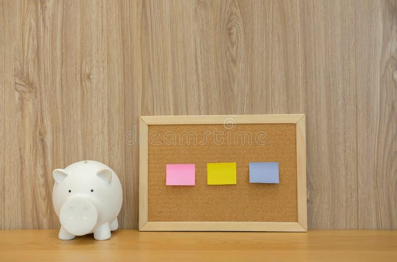 notas pegajosas na placa & no mealheiro da cortiça finança da economia do dinheiro dentro fotografia de stock