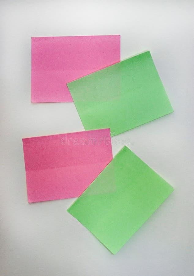 Notas - vara pegajosa verde e cor-de-rosa do gosto colorido das notas a uma parede branca fotografia de stock
