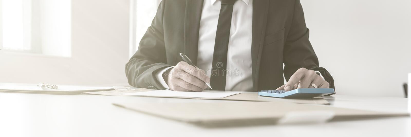 Notas y funcionamiento de la escritura del contable con una calculadora manual imágenes de archivo libres de regalías