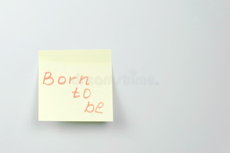 Notatka na żółtych majcheru papieru prześcieradłach z motywacją formułuje urodzonego być fotografia royalty free