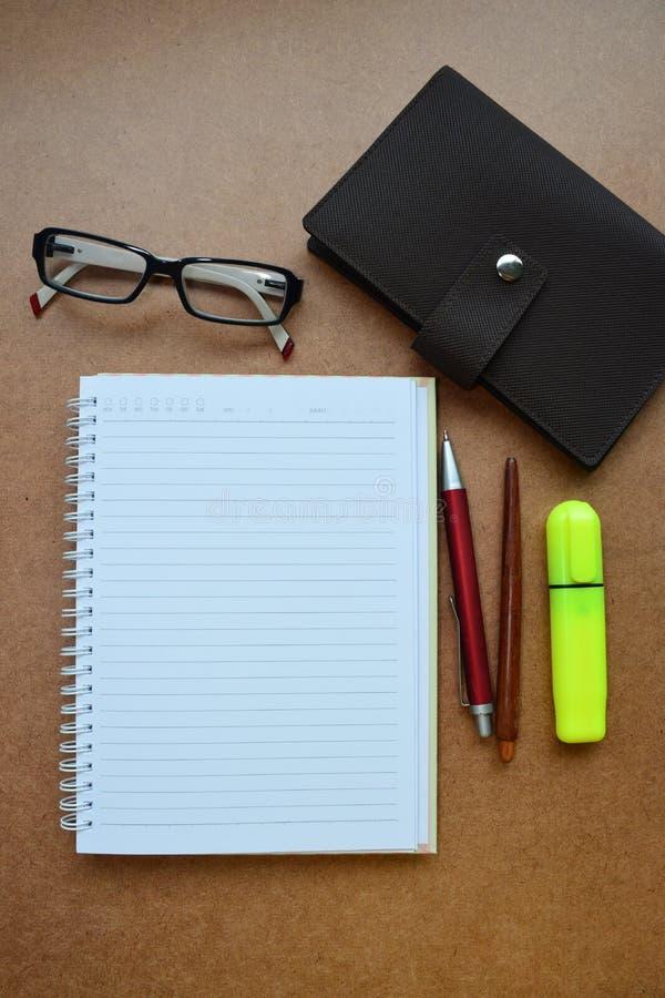 Notatnik, czerwony pióro, drewniany ołówek, markiera pióro, oczu szkła na drewnianym tle fotografia stock