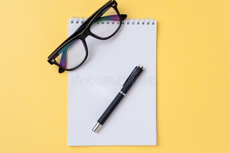 Notatnik, eyeglasses i biurowy materiały na jaskrawym żółtym tle, zdjęcie royalty free