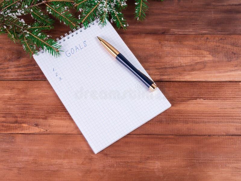 Notatnik i cele dla nowego roku drewnianego tła odgórnego widoku zdjęcia stock