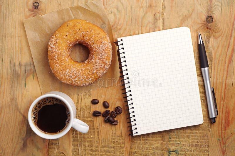 Notatnik i kawa z pączkiem zdjęcia stock
