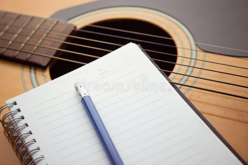 Notatnik i ołówek na gitarze zdjęcie stock