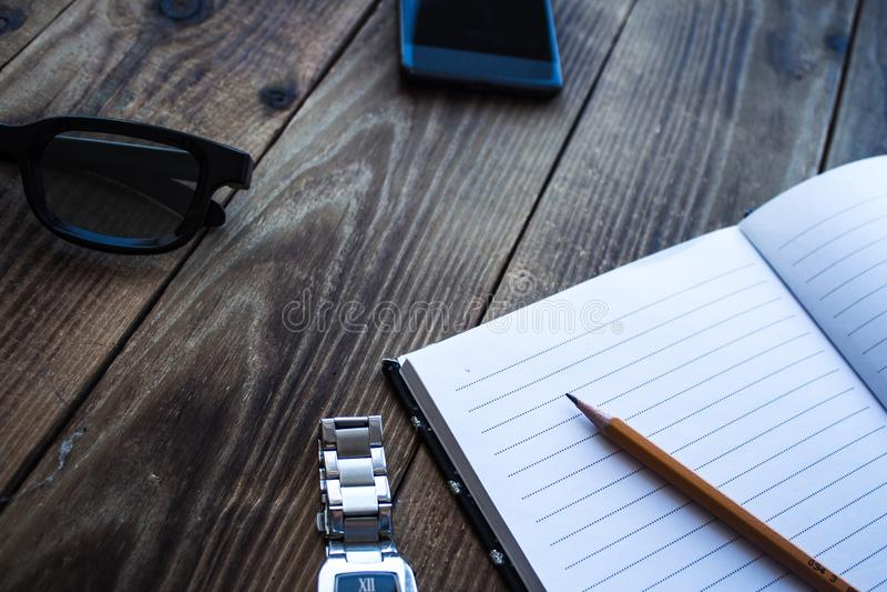 Notatnik i ołówkowy zegarek dzwonimy szkła na drewnianym bacground zdjęcia royalty free