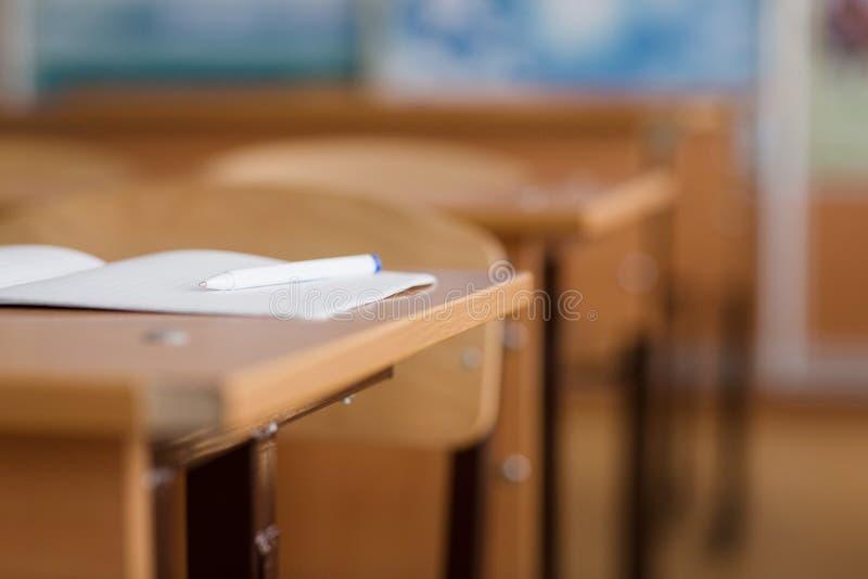 Notatnik i pióro jesteśmy na stole Szkolna sala lekcyjna w plamy tle bez młodego ucznia fotografia royalty free