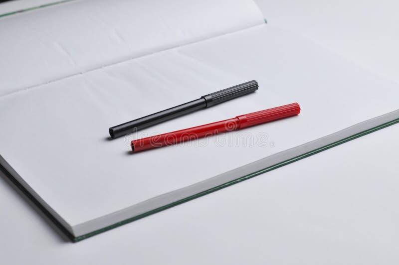 Notatnik i pióro odizolowywający na białym tle czerwieni i czerni kosmos kopii obrazy royalty free