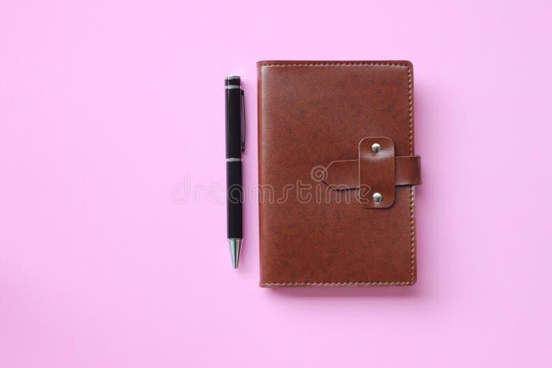 Notatnik i pióro umieszczamy na różowej podłodze i kopii przestrzeń fotografia stock