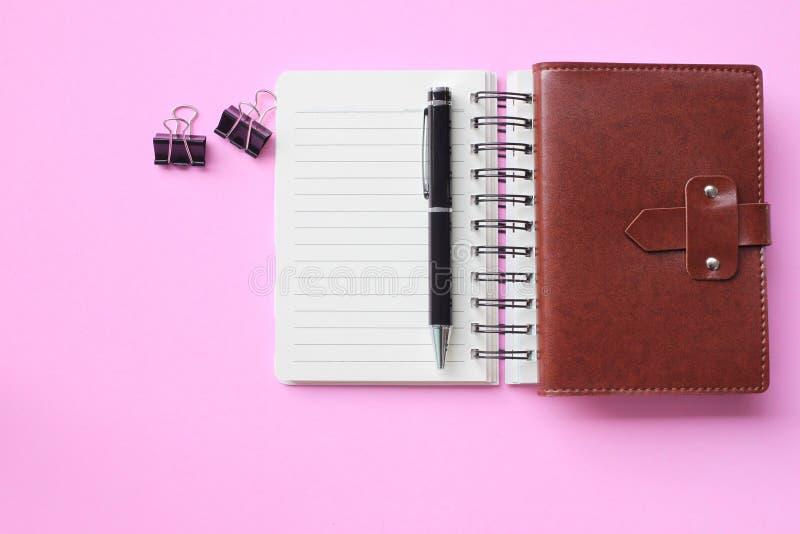 Notatnik i pióro umieszczamy na różowej podłodze i kopii przestrzeń zdjęcie royalty free