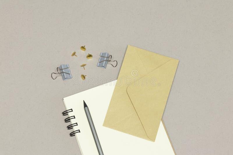 Notatnik, koperta, srebny ołówek & papierowe klamerki na popielatym tle, fotografia stock