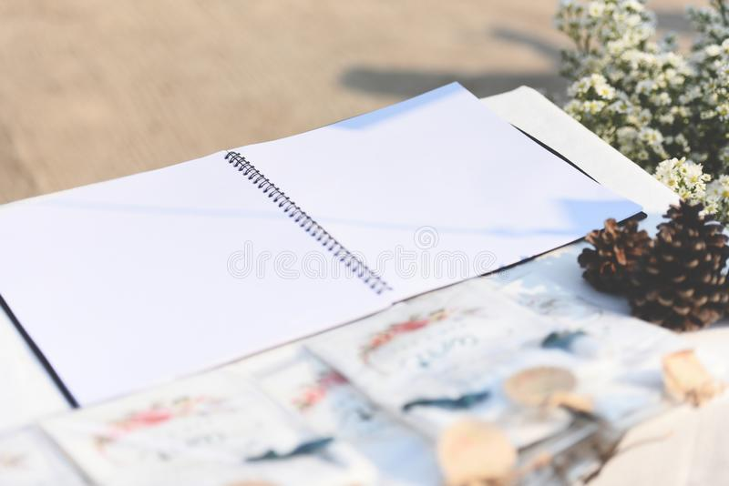 Notatnik na stołu outdoors - Pustej białej księdze obrazy stock