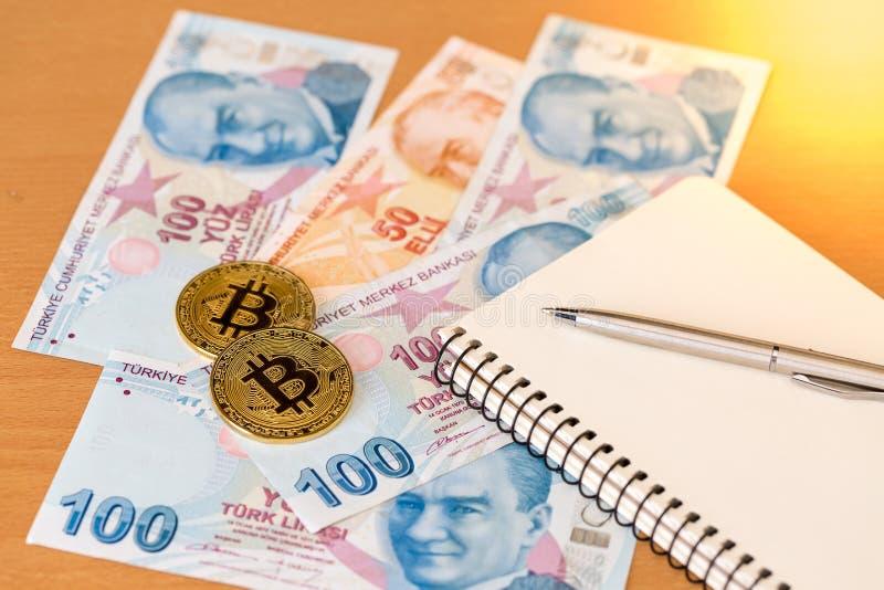 Notatnik, pióro i dwa złotego bitcoins na tureckich banknotach, fotografia stock