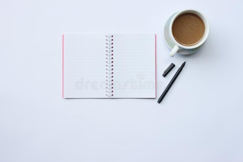Notatnik, pióro i kawowy kubek umieszczający na białym biurku W biurze, obrazy stock
