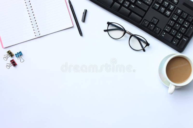 Notatnik, pióro, klawiatura i kawowy kubek umieszczający na białym biurku W t, obraz stock