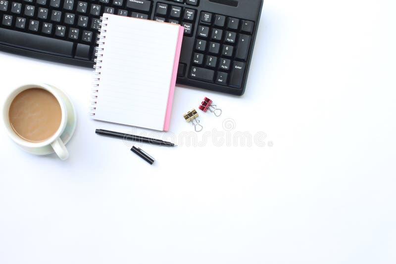 Notatnik, pióro, klawiatura i kawowy kubek umieszczający na białym biurku W t, zdjęcie stock
