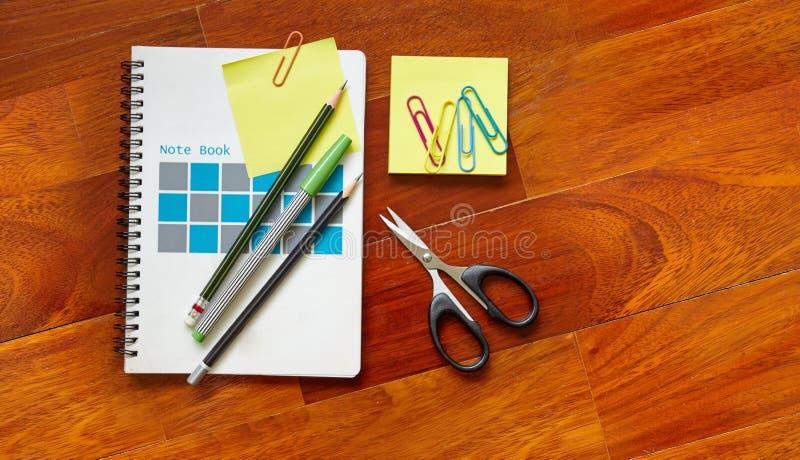 Notatnik z żółtą kleistą notatką przycinającą na okładkowej stronie, ołówkach, nożycowych na parkietowej drewnianej podłoga z kop obrazy royalty free