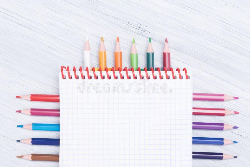 Notatnik z barwionymi ołówkami kłama pięknie na lekkim tle obraz stock