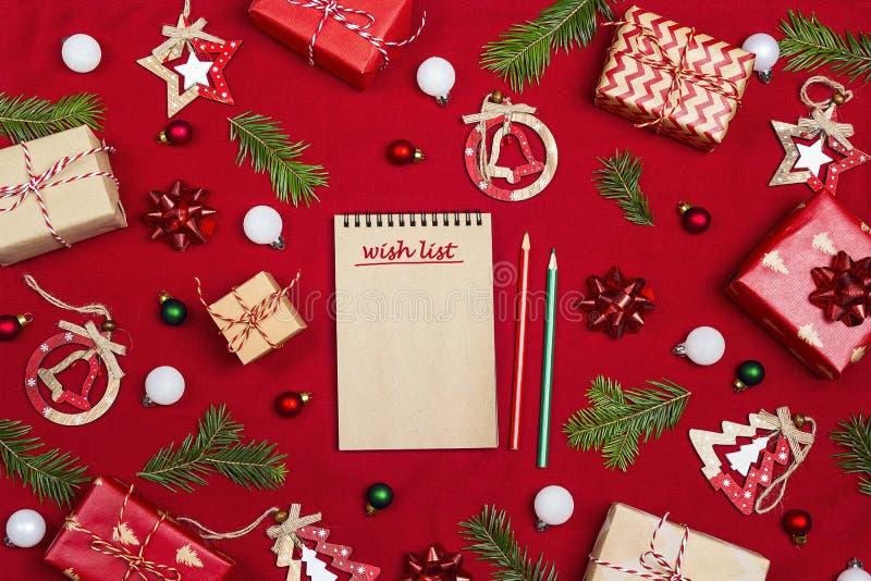 Notatnik z boże narodzenie skład prezenty i lista życzeń dekoracja na czerwonym tkaniny tle i obrazy stock