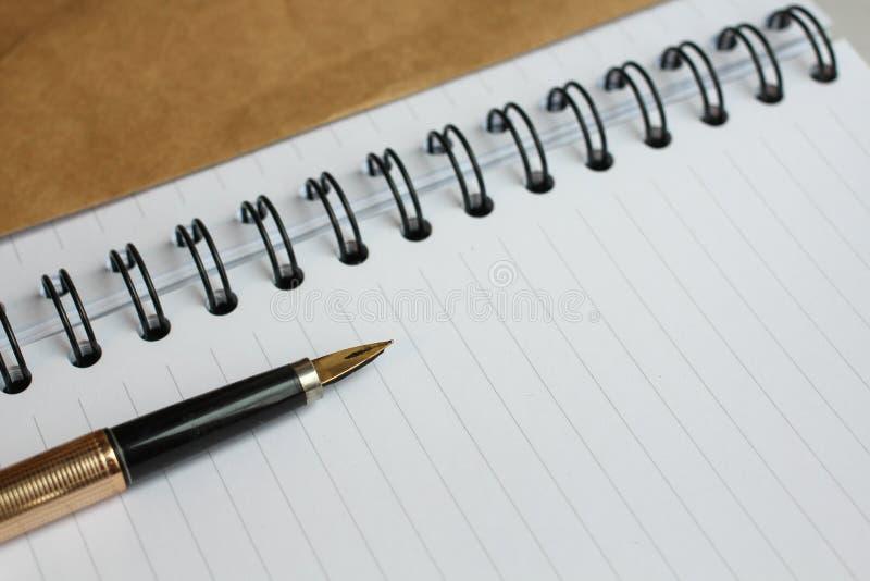 Notatnik z czystymi prześcieradłami, kopertą i złocistym piórem na stole, obraz stock